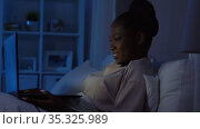 african woman with laptop in bed at home at night. Стоковое видео, видеограф Syda Productions / Фотобанк Лори