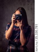 Девушка фотограф фотографирует старым фотоаппаратом, студийная фотография на сером фоне. Стоковое фото, фотограф Иванов Алексей / Фотобанк Лори
