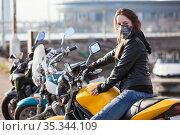 Motorcyclist Caucasian girl wearing safety mask and black leather jacket sitting on her yellow motorbike, looking at camera. Стоковое фото, фотограф Кекяляйнен Андрей / Фотобанк Лори