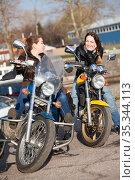 Two Caucasian women motorcyclists talk incessantly while sitting face-to-face on their motorcycles, spring season. Стоковое фото, фотограф Кекяляйнен Андрей / Фотобанк Лори