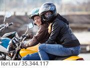 Girl a passenger sitting behind female motorcyclist on a bike, cheerful females riding on the urban street. Стоковое фото, фотограф Кекяляйнен Андрей / Фотобанк Лори