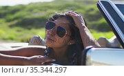 African american woman wearing sunglasses sitting in the convertible car on road. Стоковое видео, агентство Wavebreak Media / Фотобанк Лори