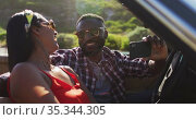 African american couple using smartphone while sitting in the convertible car on road. Стоковое видео, агентство Wavebreak Media / Фотобанк Лори