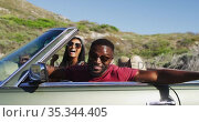 Portrait of african american couple waving and having fun while sitting in the convertible car on ro. Стоковое видео, агентство Wavebreak Media / Фотобанк Лори