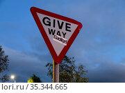 Great Britain, Northern Ireland, Belfast - traffic sign Give Way with sticker propagating the use of the Gaelic language (2019 год). Редакционное фото, агентство Caro Photoagency / Фотобанк Лори