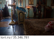 Republic of Moldova, - The first prayer in the morning in the church of Tipova Monastery at sunrise, the Pope is standing by the iconostasis (2016 год). Редакционное фото, агентство Caro Photoagency / Фотобанк Лори