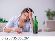 Young male alcoholic drinking whiskey at home. Стоковое фото, фотограф Elnur / Фотобанк Лори