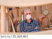 Handwerker Meister mit Maske wegen Covid-19 in seiner Werkstatt mit... Стоковое фото, фотограф Zoonar.com/Robert Kneschke / age Fotostock / Фотобанк Лори