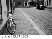 Street and bicycle by the wall in the Old Town of Stockholm (2017 год). Стоковое фото, фотограф Роман Сигаев / Фотобанк Лори