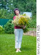 Портрет женщины средних лет с букетом полевых цветов садовом участке. Стоковое фото, фотограф Зобков Георгий / Фотобанк Лори