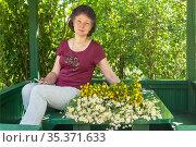 Портрет женщины средних лет с букетом полевых цветов в садовой беседке. Стоковое фото, фотограф Зобков Георгий / Фотобанк Лори