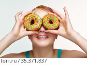 Teenager girl with unusual face art make-up . Child looking through holes in donuts. Стоковое фото, фотограф Serg Zastavkin / Фотобанк Лори