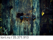 Strange scary dark rusty iron closed mystical mysterious old basement door with deadbolt lock, horror background with grunge metal texture with black shadows and glow. Стоковое фото, фотограф Светлана Евграфова / Фотобанк Лори