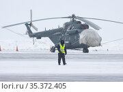A worker in a reflective vest stands on an airfield in the background of a helicopter. Стоковое фото, фотограф Константин Шишкин / Фотобанк Лори