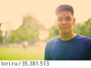 Portrait of young handsome Asian man relaxing at the park in Bangkok... Стоковое фото, фотограф Zoonar.com/Toni Rantala / easy Fotostock / Фотобанк Лори