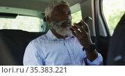 African american senior man talking on smartphone while sitting in the car. Стоковое видео, агентство Wavebreak Media / Фотобанк Лори