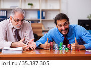 Two male employees playing cards at workplace. Стоковое фото, фотограф Elnur / Фотобанк Лори