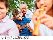 Lehrerin und Kinder zusammen im Musik Unterricht im Ferienlager oder... Стоковое фото, фотограф Zoonar.com/Robert Kneschke / age Fotostock / Фотобанк Лори