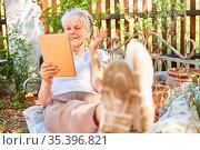 Lächelnde Seniorin im Ruhestand beim Videochat online auf der Gartenbank... Стоковое фото, фотограф Zoonar.com/Robert Kneschke / age Fotostock / Фотобанк Лори