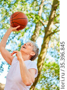 Seniorin als vitaler Rentner beim Basketball spielen für Fitness ... Стоковое фото, фотограф Zoonar.com/Robert Kneschke / age Fotostock / Фотобанк Лори