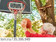 Aktiver Senior beim Basketball spielen mit Ball beim Wurf vor dem... Стоковое фото, фотограф Zoonar.com/Robert Kneschke / age Fotostock / Фотобанк Лори