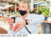 Frau als Gast mit Mundschutz am Kinn in der Kaffeepause schaut auf... Стоковое фото, фотограф Zoonar.com/Robert Kneschke / age Fotostock / Фотобанк Лори