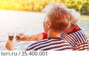 Paar Senioren beim Wein trinken am Ufer von einem ruhigen See im ... Стоковое фото, фотограф Zoonar.com/Robert Kneschke / age Fotostock / Фотобанк Лори