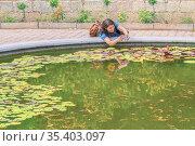 A woman photographs a lily in an artificial pond. Молодая женщина фотографирует или снимает видео при помощи смартфона цветов в искусственном водоёме. Стоковое фото, фотограф Владимир Ушаров / Фотобанк Лори