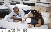 Man and woman choosing mattress in store trying it. Стоковое видео, видеограф Яков Филимонов / Фотобанк Лори