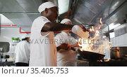 Diverse group of chefs frying in pan in restaurant kitchen. Стоковое видео, агентство Wavebreak Media / Фотобанк Лори