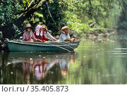 Elderly women fishing from boat on river, in rainforest. Sabah, Borneo, Malaysia. Стоковое фото, фотограф Konrad Wothe / Nature Picture Library / Фотобанк Лори