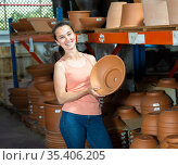 Young woman customer choosing small clay pot for garden. Стоковое фото, фотограф Яков Филимонов / Фотобанк Лори