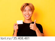 Close-up of satisfied asian guy recommend bank, showing credit card... Стоковое фото, фотограф Zoonar.com/Phongthorn Hiranlikhit / easy Fotostock / Фотобанк Лори