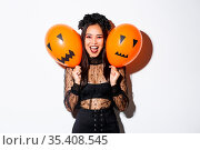 Image of asian girl in evil witch costume holding two orange balloons... Стоковое фото, фотограф Zoonar.com/Seva Levitsky / easy Fotostock / Фотобанк Лори