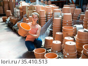 Young woman customer looking decorative clay pot for garden. Стоковое фото, фотограф Яков Филимонов / Фотобанк Лори