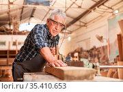 Handwerker als Schreiner Meister beim Holz hobeln in der Schreinerei... Стоковое фото, фотограф Zoonar.com/Robert Kneschke / age Fotostock / Фотобанк Лори