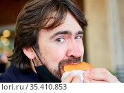 Hungriger Mann beim Burger essen mit Maske am Kinn wegen Covid-19... Стоковое фото, фотограф Zoonar.com/Robert Kneschke / age Fotostock / Фотобанк Лори
