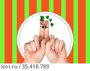 Two fingers with irish saint patrick's day themed smiling faces over red and green stripes. Стоковое фото, агентство Wavebreak Media / Фотобанк Лори