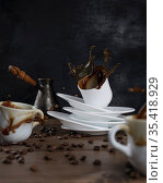 Coffee splashing out of a cups on a wooden table and black background. Стоковое фото, фотограф Александр Иванов / Фотобанк Лори