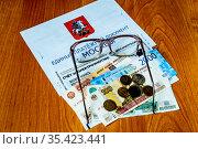 Единый платёжный документ, коммунальные платежи ЖКХ, счёт за электроэнергию очки и деньги для оплаты лежат на столе. Москва. Стоковое фото, фотограф Владимир Устенко / Фотобанк Лори