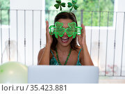 Caucasian woman celebrating st patrick's day making video call wearing deely boppers and glasses. Стоковое фото, агентство Wavebreak Media / Фотобанк Лори