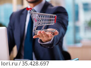 Young male employee in ecommerce concept. Стоковое фото, фотограф Elnur / Фотобанк Лори