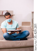 Young male student studying at home during pandemic. Стоковое фото, фотограф Elnur / Фотобанк Лори
