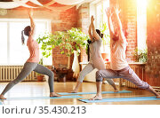 group of people doing yoga warrior pose at studio. Стоковое фото, фотограф Syda Productions / Фотобанк Лори