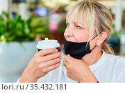 Frau mit Mundschutz am Kinn wegen Covid-19 Pandemie mit Kaffeebecher... Стоковое фото, фотограф Zoonar.com/Robert Kneschke / age Fotostock / Фотобанк Лори