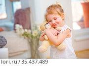 Kind kuschelt mit ihrem weichem Kuscheltier zu Hause. Стоковое фото, фотограф Zoonar.com/Robert Kneschke / age Fotostock / Фотобанк Лори