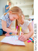 Zwei Kinder malen zusammen ein Bild auf einem Blatt Papier zu Hause. Стоковое фото, фотограф Zoonar.com/Robert Kneschke / age Fotostock / Фотобанк Лори