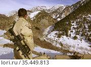AFGHANISTAN -- 12 Feb 2002 -- A Navy SEAL observes captured munitions... Редакционное фото, фотограф Jonathan William Mitchell / age Fotostock / Фотобанк Лори