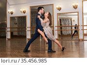 Couple practicing dancing tango in a spacious empty hall. Стоковое фото, фотограф Евгений Харитонов / Фотобанк Лори