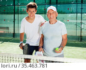 padel players of different generations posing on padel court. Стоковое фото, фотограф Татьяна Яцевич / Фотобанк Лори